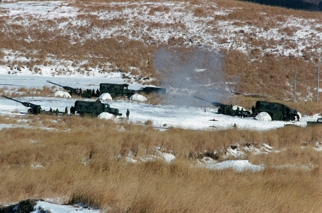 Sierra Battery, 3rd Battalion, 12th Marine Regiment, 3rd Marine Division, US Marine Corps, guns 1, 2 and 3, 155 mm M198 Howitzers fire laser guided rounds for effect. M939 series (6 X 6) 5 ton trucks are parked behind howitzers. Exercise HIJUDAI 99, Hijudai Maneuvering Area (HMA), Kyushu Island, Japan