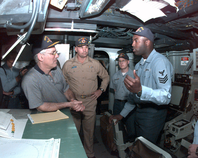 The Secretary of the Navy Richard Danzig (left) meets with GUNNER's Mate (missiles) 1ST Class (GM1) Gill Yarbrough (right) and the ships Commanding Officer Commander (CMDR) James Grant (center) in the USS FITZGERALDs (DDG 62) Combat Information Center (CIC)