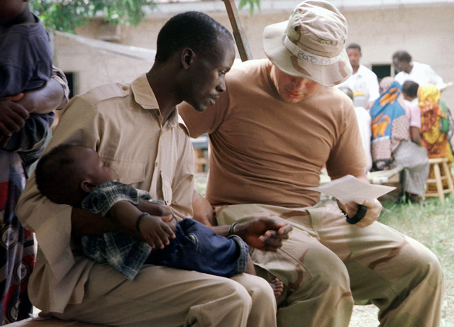 Hospital Corpsman Third Class (MH3) Chris Lugo, US NAVY (USN), assigned to 13th Marine Expeditionary Unit (MEU) Special Operations Capable (SOC) gathers vital information from a Kenyan man during humanitarian assistance operations conducted during Operation EDGE MALLET at Mombassa, Kenya