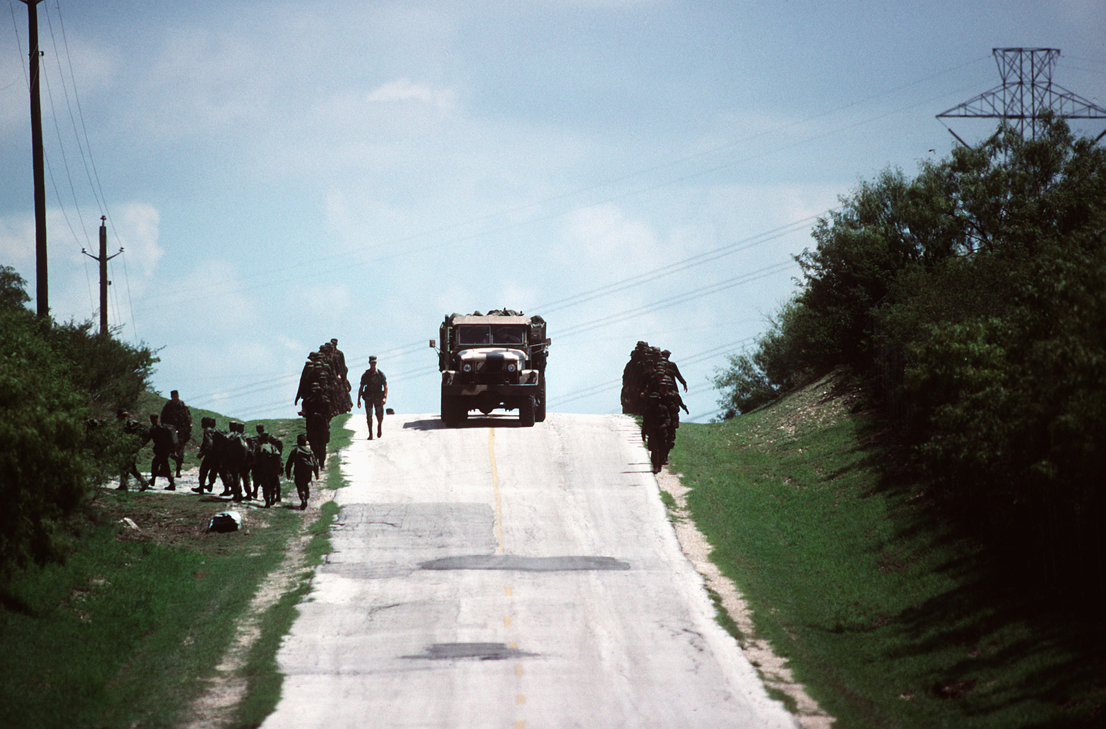 """For basic trainees at Lackland Air Force Base, Texas, a field training exercise ends with a 5.8-mile march out of """"The Scorpion's Nest,"""" and back to civilization. The trainees are being tested as they march on what they learned when simulated attacks are stages against them"""