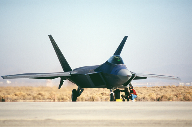US Air Force and contract maintainers with the F-22 Raptor Combined Test Force at Edwards Air Force Base, California, stand by as a F-22 pilot prepares for a test flight on March 1ST, 1999