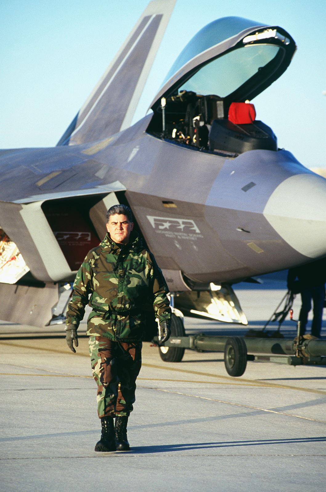 US Air Force MASTER Sergeant Joseph Chew, F-22 dedicated Crew CHIEF, walks ahead of his F-22 Raptor as it's towed for an early morning test flight on March 1ST, 1999, at the F-22 Combined Test Force Facility, Edwards Air Force Base, California