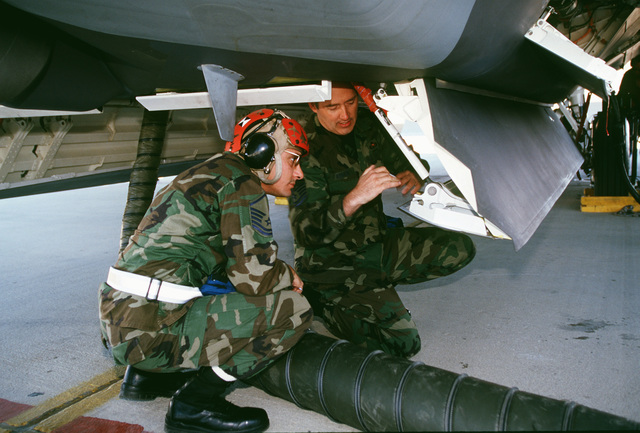 US Air Force MASTER Sergeants Tom Diaz and Mark Rediker, Armament Systems Evaluators with the F-22 Raptor Combined Test Force, discuss the hydraulic system in the F-22 weapons bay doors at Edwards Air Force Base, California, on March 1ST, 1999