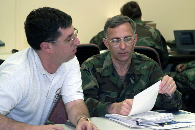 US Army Colonel Richard L. Durden, 1ST Army Deputy CHIEF of STAFF for Operations discusses Federal Emergency Management Agency (FEMA) request for sleeping cots with Ron Jones, 1ST Armys Military Planner during the 1ST Armys Joint Military Support to Civil Authorities Exercise (SRAFFEX-99). The request is based on an earthquake occurring in the New Madrid Seismic Zone. The Zone extends Northeast from Arkansas through Southeast Missouri Western Tennessee and Kentucky then northward into Southern Illinois
