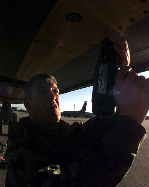 US Air Force STAFF Sergeant Darrell Bramer, a KC-135 Stratotanker Crew CHIEF, assigned to the 92nd Aircraft Generation Squadron, Fairchild Air Force Base, Washington, re-installs forward body fuel tank access panels on a KC-135 while deployed to a Moron Air Base, Spain. This mission is in direct support of Joint Task Force Noble Anvil