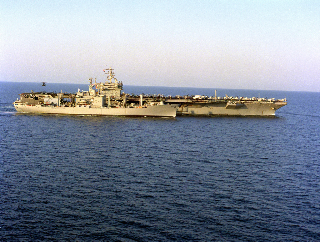 Starboard side view of the combat stores ship USS WHITE PLAINS (AFS-4) steaming alongside the nuclear-powered aircraft carrier USS ABRAHAM LINCOLN (CVN-72) in preparation for a vertical replenishment in the Gulf of Oman while both ships were operating in support of Operation Southern Watch