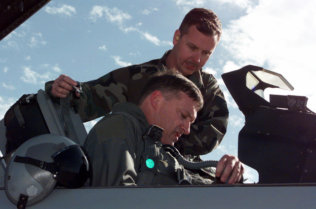 US Air Force Technical Sergeant Murray assists USAF Colonel Gary North with strapping into an F-16 Fighting Falcon aircraft prior to flying a training mission from Luke Air Force Base, Arizona. During March 1999, COL North was at Luke AFB going through F-16 refresher training before heading to Korea to become the 8th Fighter Wing commander at Kunsan Air Base. COL Gary North became the first US Air Force pilot to achieve an aerial kill in a Lockheed Martin F-16 Fighting Falcon aircraft during Operation SOUTHERN WATCH when he successfully engaged an Iraqi Mig-25 Foxbat that violated the Iraqi southern no-fly zone. COL Norths crewchief at the time of the shoot down, TSGT Murray, is now ...