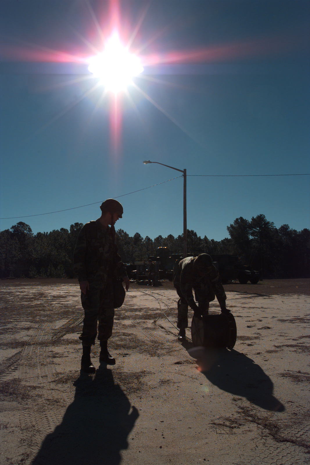 """SPECIALIST (SPC) Imdacha and Sergeant Renfro of the 67th Signal (Sig) Battalion (Bn), 93rd Sig Brigade (Bde), - 31L """"Cable Dogs"""" are running CX11230 (quarter mile coax cable) from a communication shelter to another for early morning network installation"""