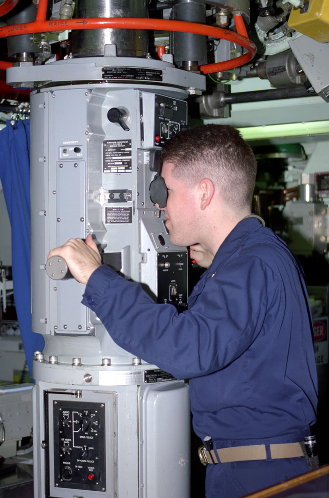 Lieutenant (LT) Barry Rodrigues, Officer of the Deck (OD), takes observations through the No. 2 periscope onboard the Los Angeles class nuclear-powered fast attack submarine USS HARTFORD (SSN 768)