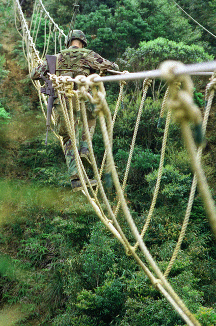 At the Jungle Warfare Training Center (JWTC), Northern Training Area, Okinawa, Japan, Lance Corporal Martinez of the First Stinger Battery, team 4, crosses the cable bridge during the endurance course