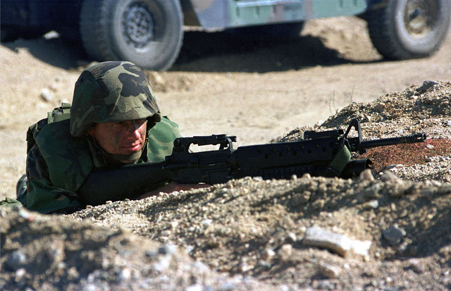 A Marine from the Wing Support Squadron 371 (MWSS-371) lays prone next to his High-Mobility Multipurpose Wheeled Vehicle (HMMWV) with his M16A2 and M203 40 mm Grenade launcher during Weapons and Tactics Instructions Class (WTI) 2-99