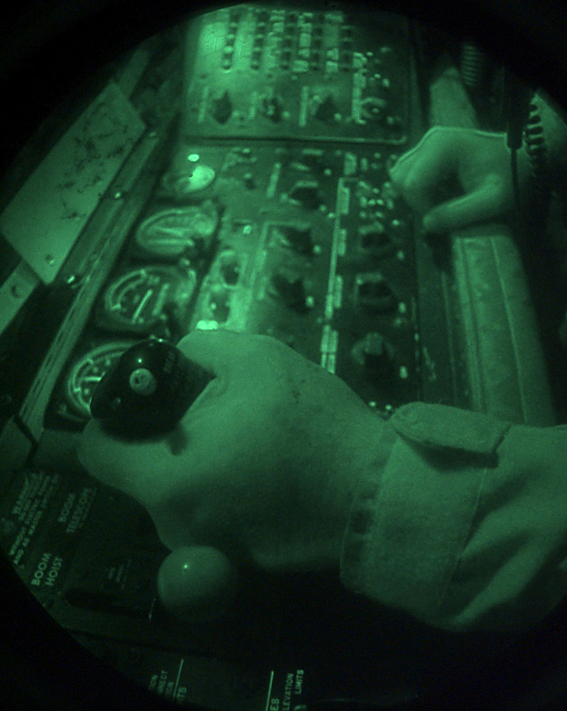 A KC-135 boom operator completes his aerial refueling checks during a mission over foreign skies in support of NATO Operation Allied Force. This image was shot through a Starlight System