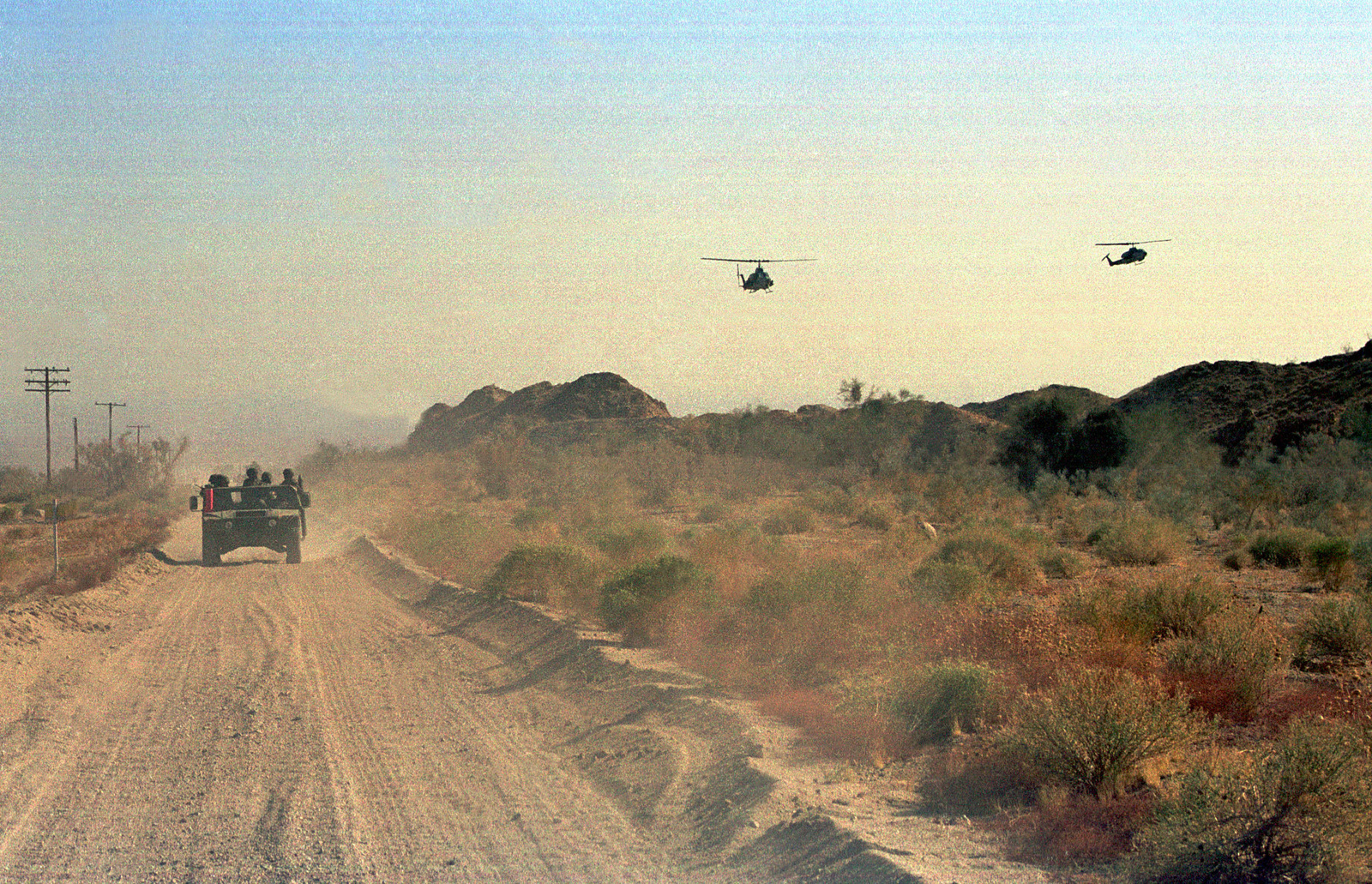 Marines from the Wing Support Squadron 371 (MWSS-371) on a reconnaissance patrol in their High-Mobility Multipurpose Wheeled Vehicle (HMMWV) are escorted by two AH-1W Cobra helicopters providing close air support during Weapons and Tactics Instructions Class (WTI) 2-99