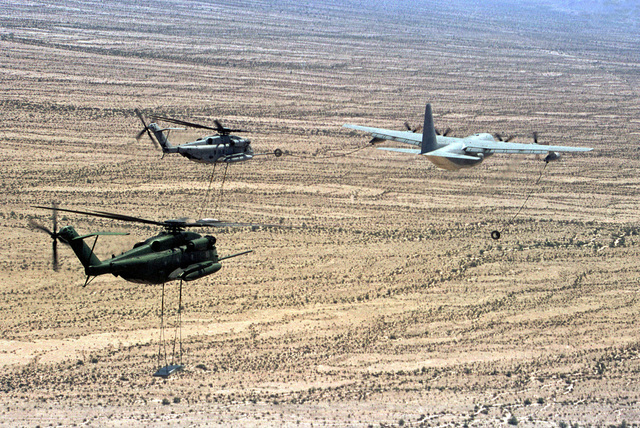 Two Marine CH-53E Sea Stallion helicopters lifting cement slabs simulating High-Mobility Multipurpose Wheeled Vehicle (HMMWV) link-up for an air-to-air refueling with a KC-130F Aerial Tanker during Weapons and Tactics Instructions Class (WTI) 2-99