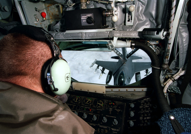 The view over the shoulder of a boom operator with the 351st Air Refueling Squadron based at RAF Mildenhall United Kingdom, looking to the rear of the 100th Air Expeditionary Wing KC-135R Stratotanker on 31 Mar 99. The receiver is an F-16C Falcon from the 52nd Fighter Wing based at Spandahlem AB Germany. It is armed with AIM-120C missiles for self protection and Highspeed Anti-Radiation Missiles to suppress anti-aircraft radar sites. This mission is in direct support of NATO Operation Allied Force