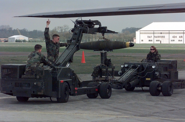 A bomb loading team from Ellsworth Air Force Base, South Dakota, download Mark-82 gravity bombs with two MHU-83 B/E Lift Trucks, from a B-1B Lancer (partially shown) at RAF Fairford, United Kingdom. The B-1B is a long-range strategic bomber capable of flying intercontinental missions and penetrating present and future sophisticated enemy defenses. Five Lancers are forward deployed to the U.K., in support of NATO Operation Allied Force in the former republic of Yugoslavia