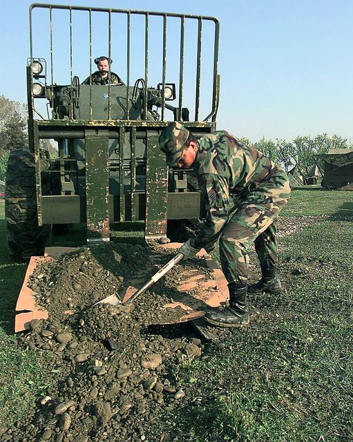 A Heating, Ventilation, Air Conditioning Repair Technician with the 86th Contingency Response Group, fills ditches around the base camp at Tirana, Albania, to prepare tents (not shown) for newly arriving personnel. The 86th CRG from Ramstein AB, Germany, deployed to Tirana, Albania April 4, 1999, as the lead element of the U.S. Humanitarian Relief Force Shining Hope to distribute rations and water to United Nations High Commissioner for Refugees