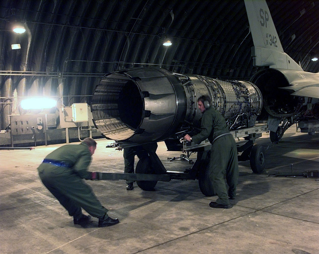 U.S. Air Force crew chiefs position an engine for installation in an F-16 Fighting Falcon on April 7, 1999. Members of the 23rd Fighter Squadron, Spandahelm Air Base, Germany, are deployed to Aviano Air Base, Italy, in support of NATO Operation Allied Force