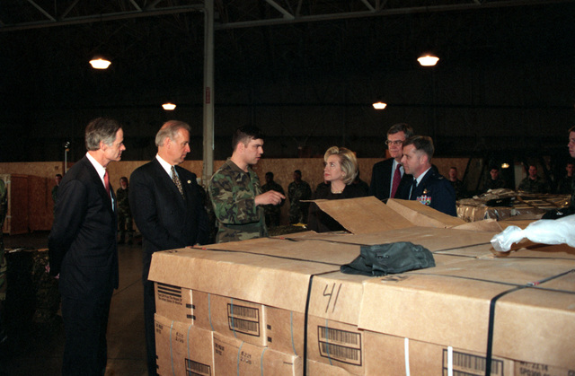 Left side front view, medium shot from the waist up of US First Lady Hillary Rodham-Clinton as she stands behind pallets of Meals Ready to Eat (MRE). USAF Technical Sergeant Robert Graber Jr., Non-Commissioned Officer in Charge (NCOIC) of the 436th Super Port Cargo Processing Section, Dover Air Force Base, Delaware, explains to the First Lady how the humanitarian relief pallets are built up and processed through the supply system at Dover