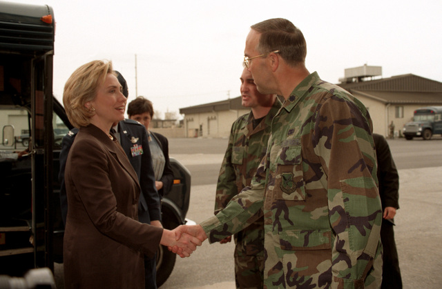 Right side profile, medium shot of US First Lady Hillary Rodham-Clinton as she's greeted by USAF Lieutenant Colonel Paul Curtis, Commander 436th Aerial Port Squadron, Dover Air Force Base, Delaware. Mrs. Clinton was given a tour of the Super Port facility (Not shown). The port is a staging area for humanitarian relief supplies that are processed and moved onto Kosovo