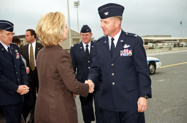 Right side rear view, medium shot of US First Lady Hillary Rodham-Clinton as she's greeted by USAF Colonel Felix Grieder, Commander 436th Airlift Wing, Dover Air Force Base, Delaware, upon her arrival to the base on April 9th, 1999