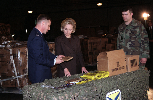 Straight on medium shot of US First Lady Hillary Rodham-Clinton as USAF Colonel Felix Grieder, Commander 436th Airlift Wing, Dover Air Force Base, Delaware, shows her how the humanitarian relief meals ready to eat (MRE), are packed before processing and shipping to the Kosovo refugees (Refugees not shown)