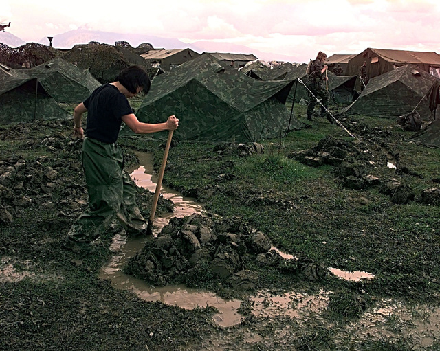 TSGT Theresa Penn, Detachment 6, 7th Weather Squadron, Wiesbaden, Germany, digs drainage ditches at the U.S. encampment at Tirana, Albania. Penn and other U.S. forces are part of the U.S. contingent sent to Albania in support of Operation Sustain Hope, the U.S. effort to bring in food, water, medicine, relief supplies, and to establish camps for the refugees (not shown) fleeing from the Former Republic of Yugoslavia into Albania and Macedonia