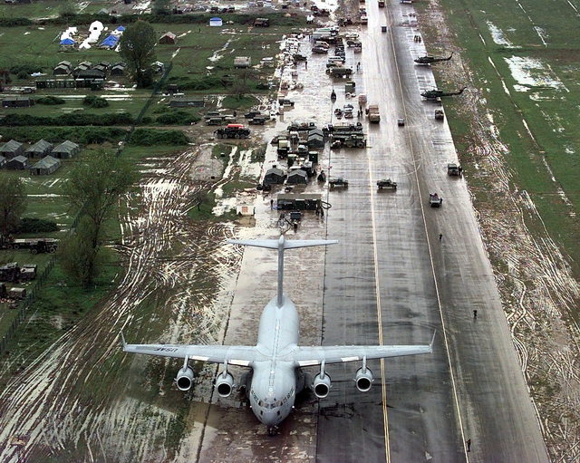An aerial view of a C-17 Globemaster III from Charleston Air Force Base, North Carolina, arriving from Ramstein Air Base, Germany offloads U. S. Army personnel at Tirana airfield, Albania, the base camp for members of Operation Sustain Hope. Joint Task Force (JTF) Operation Sustained Hope, is a combined NATO and joint U.S. military humanitarian relief effort, in conjunction with civilian relief agencies. Sustained Hope is bringing relief to thousands of refugees (not shown) in Albania displaced by the current unrest in the region of Kosovo, Yugoslavia