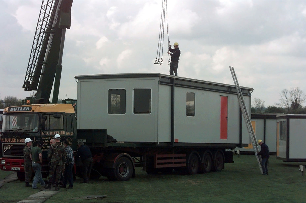 Air Force civil engineers and civilian contractors attach a portable shelter to a crane at Royal Air Force Fairford, England. The population of the English base has expanded three fold in the last two months due to the influx of people in support of NATO Operation Allied Force. The portable shelters will be used to augment existing dormitories