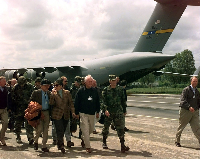COL Clifton Bray, American Task Force commander for Joint Task Force Shining Hope, takes US congressman and senators on a tour of the Rinas flight line during their tour in Albania, Apr. 17, 1999. Congressman Bill Young, Republican from Florida's 10th District, walks to the right of COL Bray (screen left). To his right is the US Ambassador to Albania, Marisa Lino and to her right is US Senator Ted Stevens, Republican from Alaska. A Charleston C-17 from the 437th Air Mobility Wing, transported the visitors to and from Albania. This mission is in direction support of Operation Sustain Hope