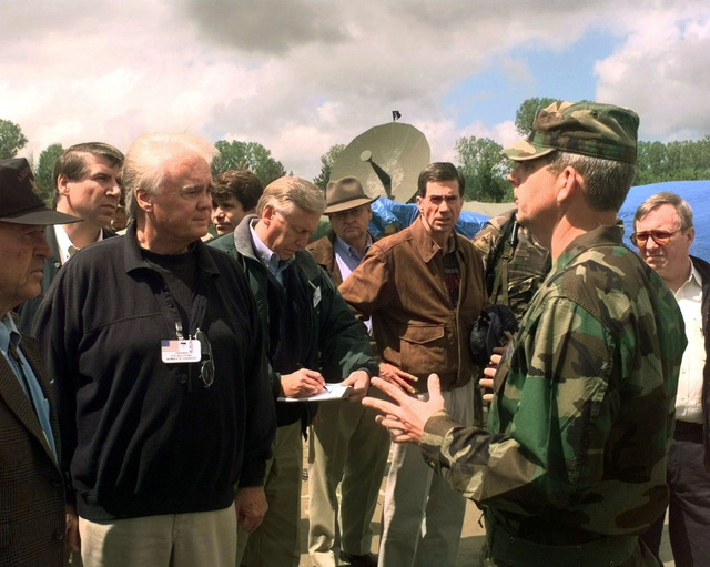 COL Clifton Bray, American Task Force commander for Joint Task Force Shining Hope, takes US congressman and senators on a tour of the Rinas flight line during their visit in Albania. Congressman Bill Young, Republican from Florida's 10th District, faces the camera at the left of the frame. US Senator Charles Robb, Democrat from Virginia, stands with his hands on his hips in a suede jacket. This mission is in direction support of Operation Sustain Hope