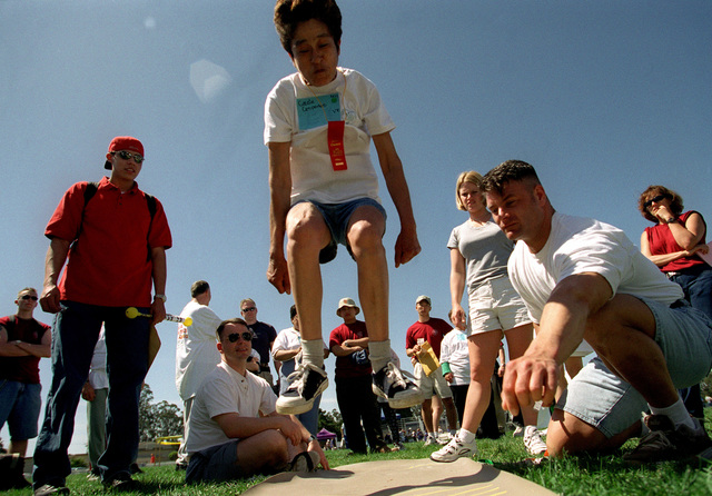 US Air Force STAFF Sergeant Kirby Ross, 30th Mission Support Squadron (MSS) (Right), is ready to mark Cosie Espedes' standing long jump as spectators watch and cheer her on. The long jump was just one of the many events, at the '99 Northern Santa Barbara County Special Olympic Games held on April 17th, 1999 at Vandenberg Air Force Base, California. This image is seen in the April 1999 edition of AIRMAN Magazine