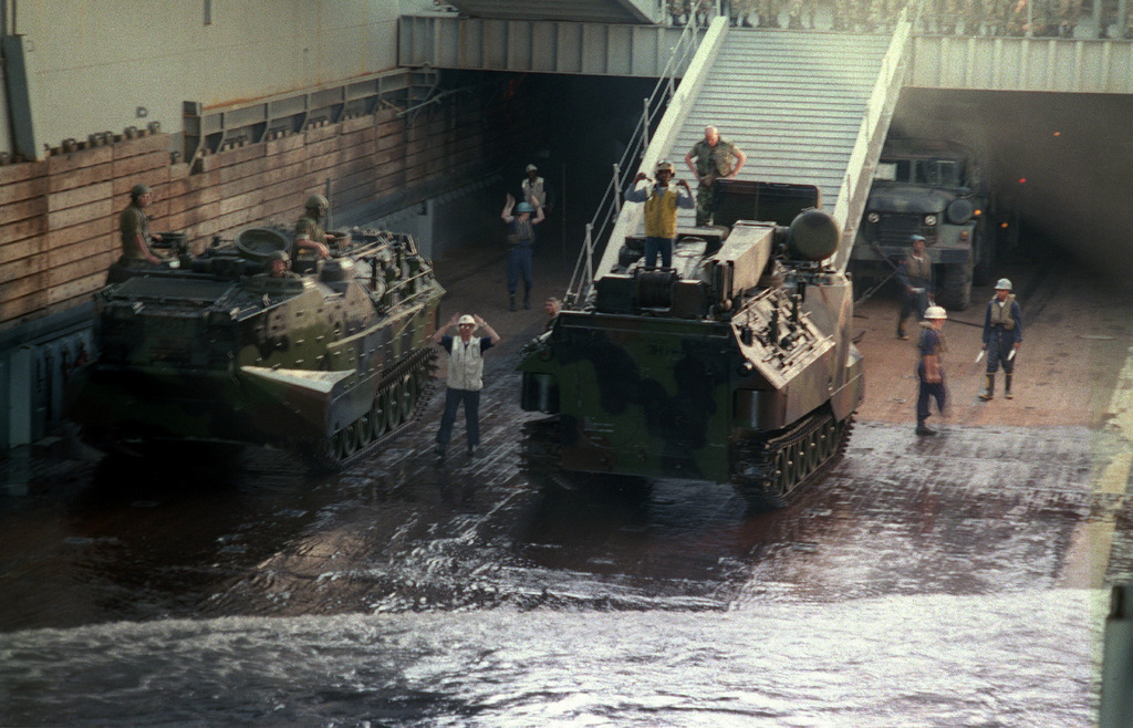 Amphibious Assault Vehicles (AAV7A1) are ground guided into their assigned positions in the enormous well deck on board the USS Anchorage (LSD-36) during Exercise KERNEL BLITZ '97, held at Camp Pendleton, California. KERNEL BLITZ is a bi-annual Commander-in-CHIEF Pacific (CINCPAC) fleet training exercise (FLEETEX) focused on operational/tactical training of Commander, Third Fleet (C3F)/ I Marine Expeditionary Forces (MEF) and Commander, Amphibious Group 3 (CPG-3)/ 1ST Marine Division (MARDIV). KERNEL BLITZ is designed to enhance the training of Sailors and Marines in the complexities of brigade-size amphibious assault operations
