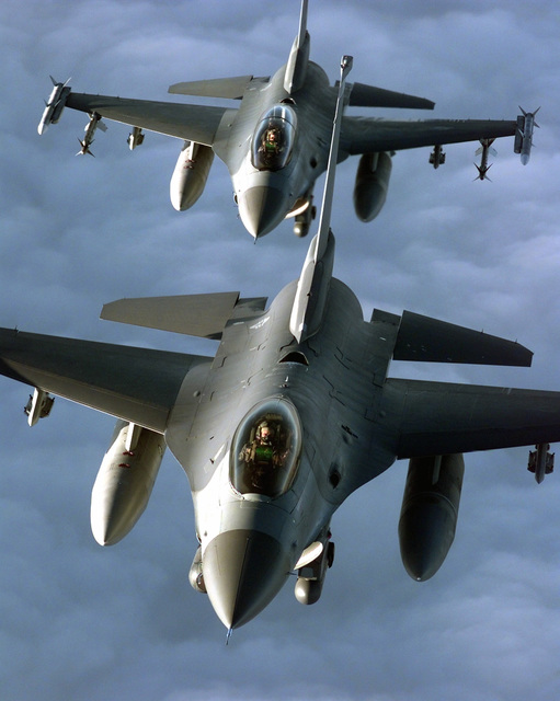 "Two United States Air Forces Europe F-16Cs fly in formation during a mission in support of NATO Operation Allied Force. The F-16s are from the 510th Fighter Squadron ""Buzzards"", Aviano Air Base, Italy and are carrying a full air-to-air combat load to include AIM-120 missiles, drop tanks and a electronic jamming pod. The lead F-16 is a single seat F-16CG and has both a laser designating pod as well as a FLIR (Forward Looking Infrared) pod on the intake sides. The second F-16 is a F-16DG and is only capable of carrying the FLIR pod. Both F-16s are flying missions in suport of the ongoing NATO Operation Allied Force"
