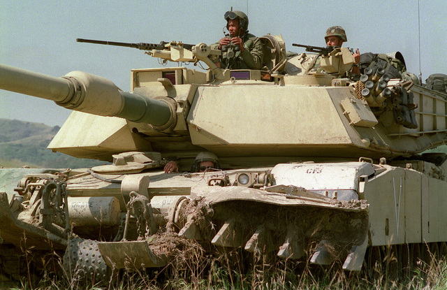 Medium shot, left side front view of a desert camouflaged M1A1 Abrams tank with a mine plough system. The tank commander, loader and driver are outside their turrets. The commander mans the 12.7mm machine gun. The loader mans a 7.62mm machine gun. The crew, from 1ST Tanks, 1ST Marine Division observe the surrounding area during Kernel Blitz '99 at the US Marine base at Camp Pendleton, California