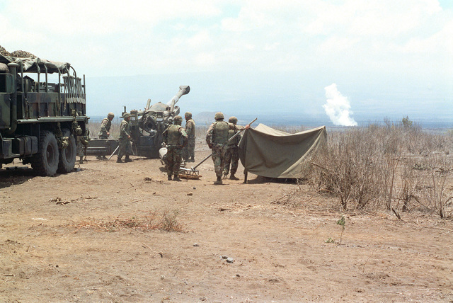 Marines from Bravo Battery, 1ST Battalion, 12th Marines, 3rd Marine Regiment wait for the next stage of fire for a M198 155mm Towed Howitzer during a combined arms live fire exercise. The M198 is constructed of aluminum and steel, and is air transportable by CH-53E helicopter and C-130 or larger fixed-wing aircraft. Maximum effective range with conventional ammunition is 22,400 meters (13.92 miles) and with a rocket-assisted projectile, 30,000 meters (18.64 miles)