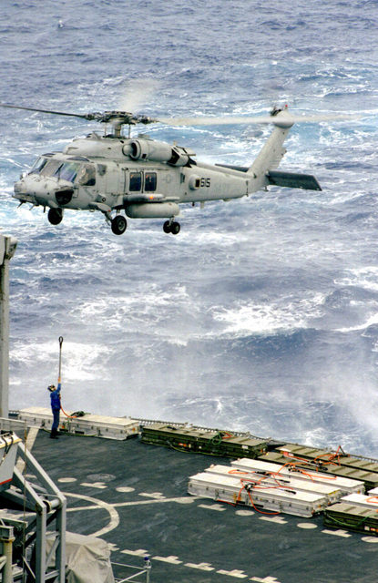 "An SH-60F ""Seahawk"" assigned to the ""Tridents"" of Helicopter Anti-Submarine Squadron Three (HS-3) receives its next load of weapons from the fast combat support ship USS Arctic (AOE 8) (not shown) during vertical replenishment operations at sea. THEODORE ROOSEVELT and Arctic are currently deployed in support of the NATO-led operations ""Allied Force"""