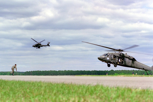 "A pilot from the 157 Fighter Squadron, 169th Fighter Wing, South Carolina Air National Guard is ""rescued"" by a UH-60 Blackhawk, as a AH-64 Apache provides cover in background, during a simulated combat search and rescue mission. Demonstrated at the SC ANG's Air Show on 2 May 2 1999 at McEntire Air National Guard Base, South Carolina"