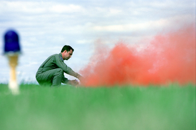 A pilot from the 157 Fighter Squadron, 169th Fighter Wing, South Carolina Air National Guard sets off a colored smoke flare to mark his position during a simulated combat search and rescue mission. Demonstrated at the SC ANG's Air Show on 2 May 1999, McEntire Air National Guard Base, South Carolina