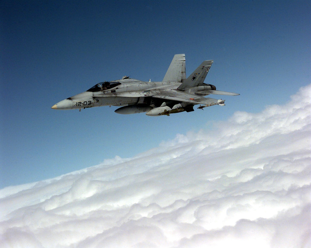 A Spanish Air Force EF-18A Hornet moves into position behind an Air Combat Command KC-135R Stratotanker (not shown) of the 22nd Air Refueling Squadron during a NATO Operation Allied Force Combat Mission. The versatility of the KC-135 Stratotanker is clearly demonstrated by its ability to adapt quickly to each mission. This mission required that the tanker attach a refueling drogue (not shown) to the end of its refueling boom (not shown) so that NATO aircraft fitted with a refueling probe could refuel. The EF-18A Hornets carries AIM-9 Sidewinder missiles on the wingtip rails, MK 82 500 pound Laser Guided Bombs in the middle of the wings and 350 gallon underwing drop tanks to extend mission...
