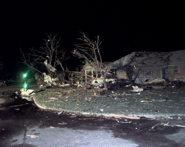 Looking like a war zone, this area in Oklahoma City, Oklahoma, was devastated by an F-5 Tornado with winds up to 230 miles per hour. The area of destruction was 1 mile wide and and left a path of destruction 19 miles long. This night time image shows a partially damaged home with debris in the front yard to include several items stuck in two leafless trees