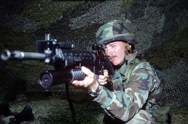 Michael Pettit, a team member with the Security Forces Squadron, aims his M16 rifle at an electronic simulated target, generated by a Combat Simulator, during GUARDIAN CHALLENGE 99