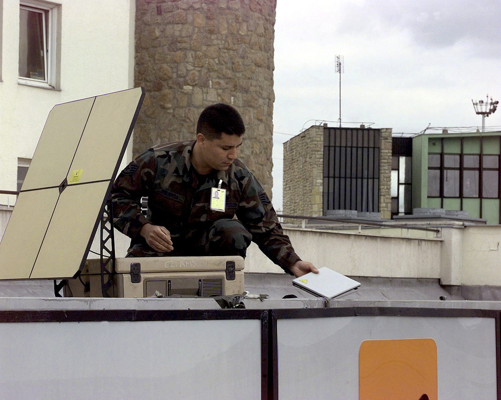 US Air Force STAFF Sergeant Richard Figueroa, a Communications/ Aircraft Generation Equipment SPC., assigned to the 621st TALCE (Tanker Air Lift Control Element) McGuire Air Force Base, New Jersey, sets up a satellite communications system during the initial bed down in Budapest Hungary. This mission is in direct support of Operation Allied Force