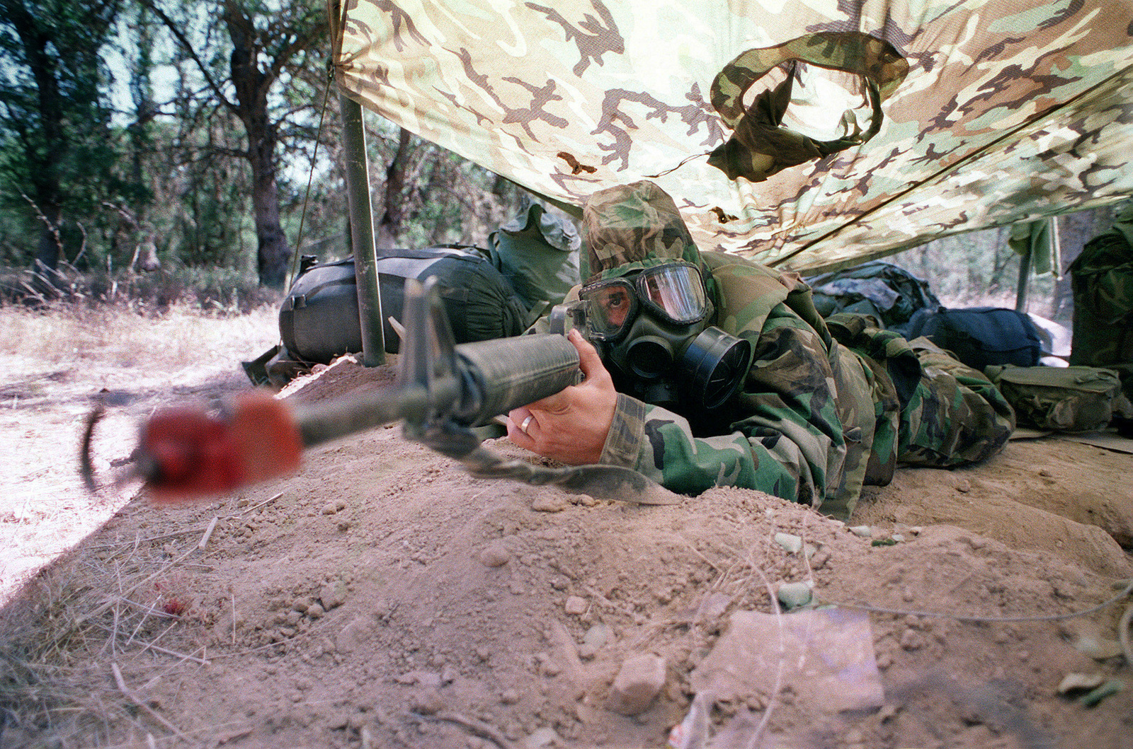 A US Marine from the Second Battalion, Fifth Marines, Headquarters Company, as he takes a position during a simulated Nuclear Biological Chemical (NBC) attack Mission-Oriented Protective Posture response level 3 (MOPP-3) during Exercise Sea Horse Wind at Fort Hunter Liggett in Jolon, California