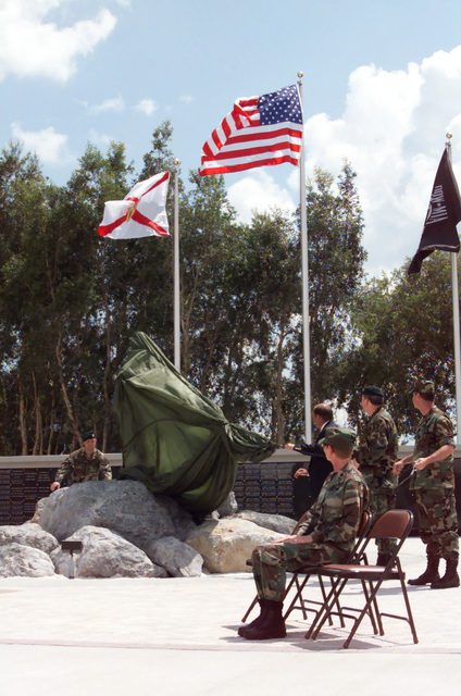 Straight on medium of three unidentified individuals as they remove the cover to the Warrior Statue that's part of the United States Special Operations Command (USSOCOM) Memorial. The dedication ceremony sponsored by the Special Operations Memorial Foundation, took place on May 24th, 1999, at MacDill Air Force Base, Florida