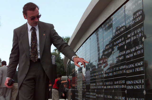 Straight on, medium shot from a low angle, up at former Army Sergeant Bill Barcy, Special Forces, as he points to names of fallen comrades engraved on the Special Operations Memorial. A dedication ceremony, sponsored by the Special Operations Memorial Foundation, took place on May 24th, 1999, at MacDill Air Force Base, Florida