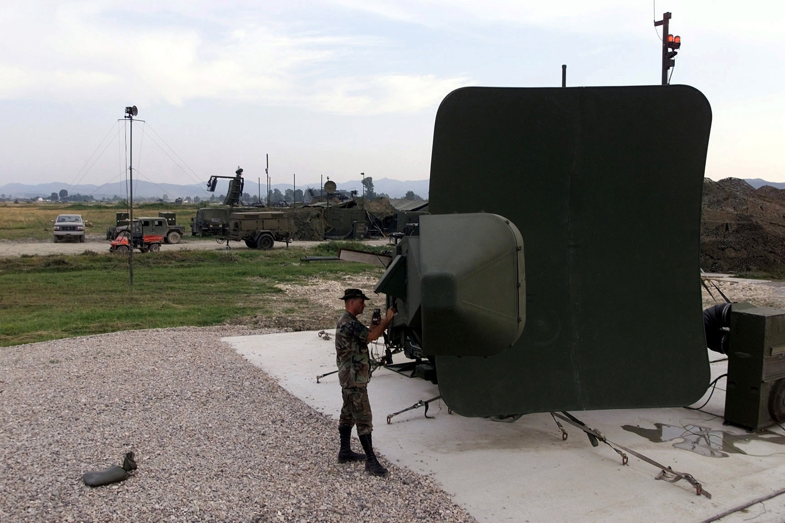 Right side profile, long shot from a high angle of MASTER Sergeant Steven Neal, 1ST Combat Communications Squadron, Ramstein Air Base, Germany, as he uses a multimeter to check the phase shifter power supply on the Precision Approach Radar. Members of 1ST Combat Communications are deployed to Albania in support of operation Shining Hope