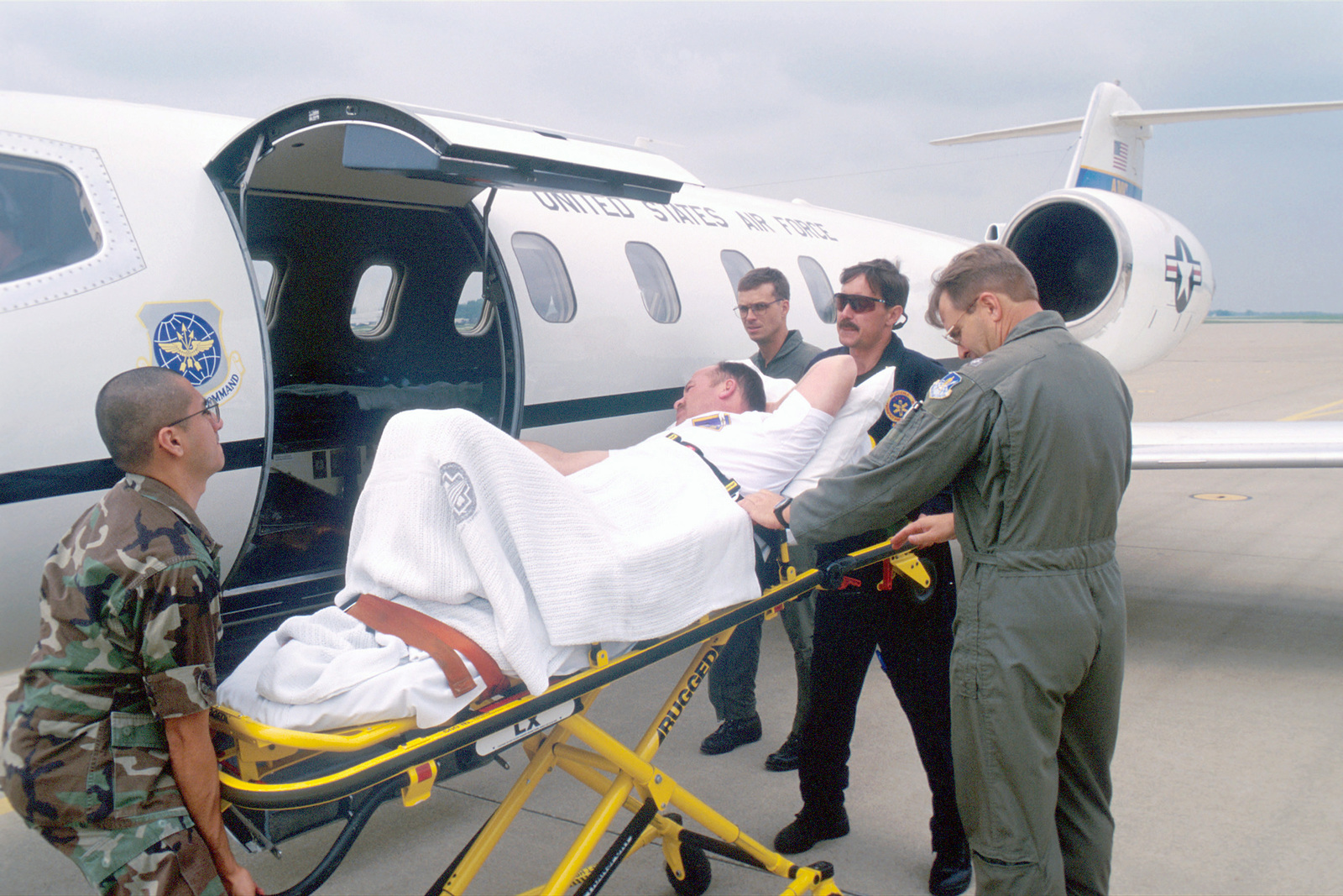 Aircrew and emergency medical technicians load Allen aboard the C-21 at Fort Campbell, Kentucky. Sergeant First Class Michael Allen was injured during paratrooping duty. The patient, Allen, was transferred to Walter Reed Medical Center in Washington, D.C. AIRMAN Magazine's Article Air Care by Technical Sergeant Pat McKenna describes the airborne ambulances mission and history in celebration of the 50th anniversary of medical services. (AIRMAN Magazine/July 1999)