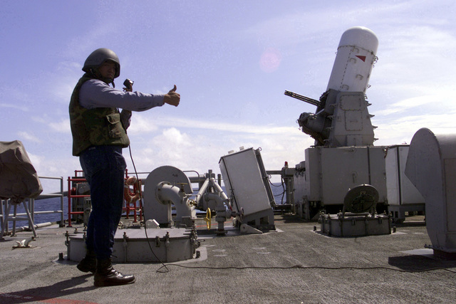 US Navy Fire Control Technician 3rd Class Jay Batoon acts as safety observer and signifies the OK as USS REUBEN JAMES (FFG 57) prepares to test fire its CIWS (Close-In Weapons System) off the northwest coast of South America while en route to Exercise TEAMWORK SOUTH '99. Reuben James will be conducting bilateral operations with the Chilean navy. (Substandard image)