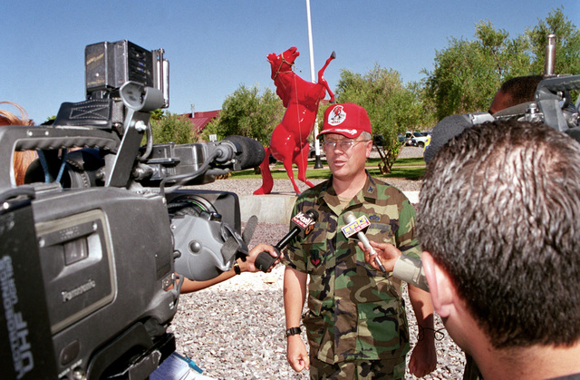 Straight on medium shot of USAF Colonel Richard Parker, 820th Red Horse Squadron Commander as he answers questions at a news conference about their deployment to Albania for critical road and bridge repairs. News reporters and videographers are seen in the foreground. A statue of a red horse rearing up on its hind legs is seen in the background. This image was taken on June 8th, 1999